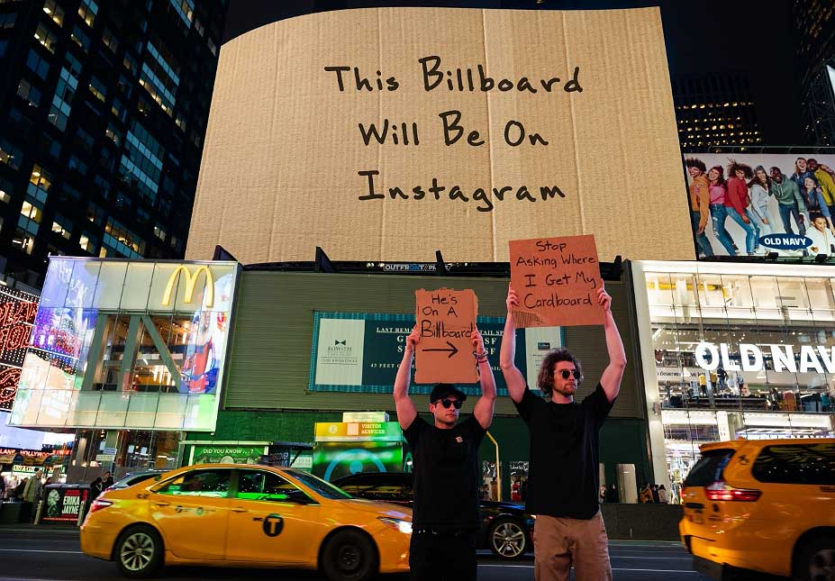 outfront media out of home advertising with dude with sign instagram