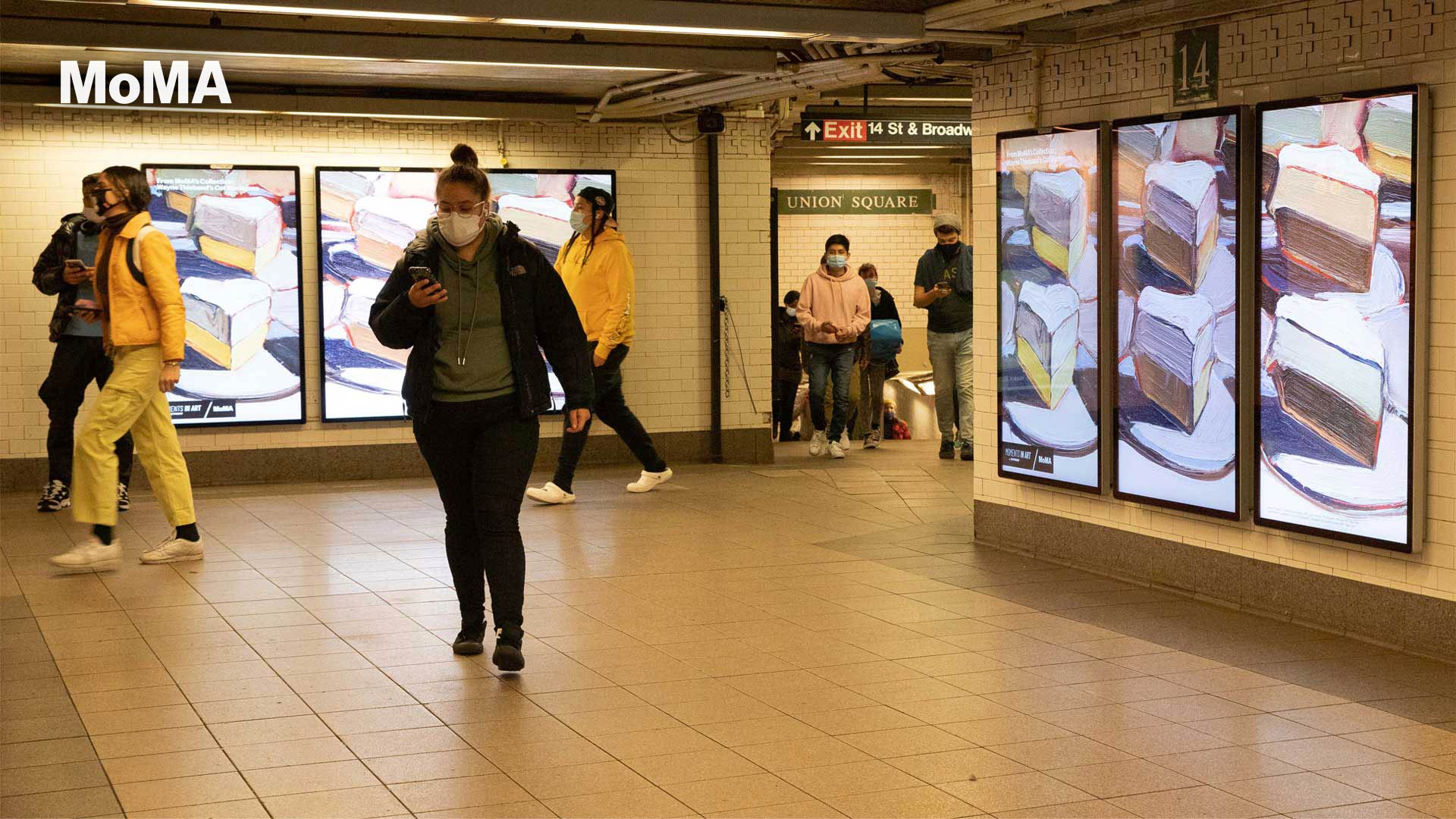 Triptych digital display of MoMA art in subway station